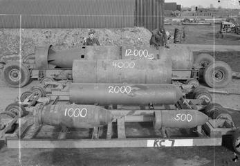 Armourers show off bombs for a comparison in size at the bomb dump at Woodhall Spa, Lincolnshire. In the front are 1,000-lb and 500-lb MC bombs, behind them a 2,000-lb HC Mark I, then a 4,000-lb HC Mark III or Mark IV 'Cookie'. Finally, at the rear, is a 12,000-lb HC 'Blockbuster', essentially three 4,000-lb 'Cookies' bolted together with the addition of a six-finned ballistic tail.