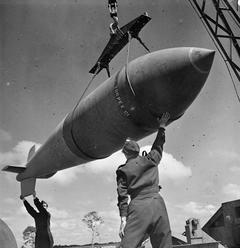 © IWM (CH 15363) A 12,000-lb MC deep-penetration bomb (Bomber Command executive codeword 'Tallboy') is hoisted from the bomb dump to its carrier at Woodhall Spa, Lincolnshire, to be loaded into an Avro Lancaster of No. 617 Squadron RAF for a raid on the V-weapon site at Wizernes, France, 22 June 1944. 617 Squadron were unable to bomb the target on this occasion because of low cloud cover, but were to succeed two days later.