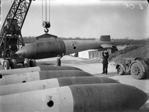 A 26 foot long 22,000-lb MC high explosive deep-penetration bomb (Bomber Command executive codeword 'Grand Slam') is manoeuvred onto a trolley by crane in the bomb dump at Woodhall Spa, Lincolnshire, for an evening raid by No. 617 Squadron RAF on the railway bridge at Nienburg, Germany. 20 aircraft took part in the raid and the target was destroyed. CH 15369 Part of AIR MINISTRY SECOND WORLD WAR OFFICIAL COLLECTION Royal Air Force official photographer Crouch F W (Flt Lt)